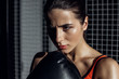 Concentrated pretty boxer in black boxing glove looking away