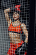 Attractive boxer standing behind wire netting and looking away