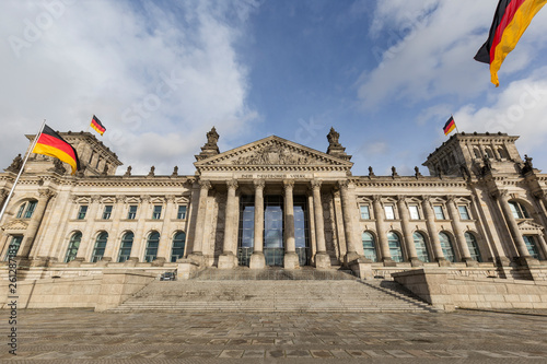 German flags and front view of the German parliament building Reichstag  in Berlin. The Reichstag building is the seat of the German Bundestag since 1999 and it was originally built from 1884 to 1894. © tuomaslehtinen