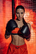 Boxer in boxing gloves and briefs standing near wire netting and looking at camera