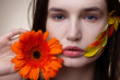 Close up of model with natural look holding nice orange flower