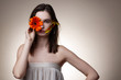 canvas print picture - Beautiful model hiding half of her face with orange flower