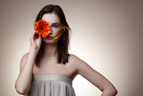 Beautiful model hiding half of her face with orange flower