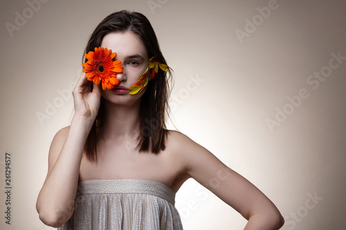 canvas print picture Beautiful model hiding half of her face with orange flower