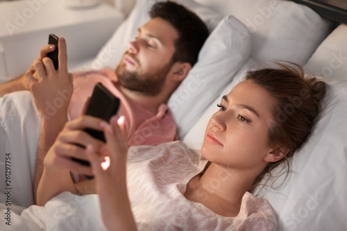 Leinwandbild Motiv technology, internet and communication concept - couple using smartphones in bed at night