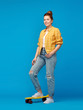 Leinwandbild Motiv leisure, sport and people concept - smiling red haired teenage girl in checkered shirt and torn jeans with short skateboard over bright blue background