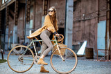 Full body portrait of a beautiful stylish woman dressed in coat standing with retro bicycle outdoors on the industrial urban background