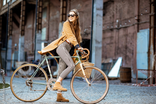 canvas print picture Full body portrait of a beautiful stylish woman dressed in coat standing with retro bicycle outdoors on the industrial urban background