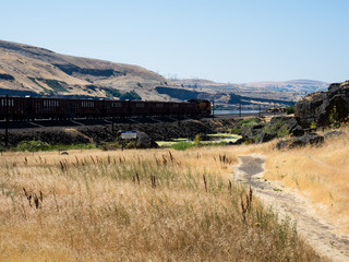 Dallesport, WA, USA - July 24, 2017: Freight train running along Columbia River Gorge in eastern Washington State