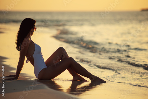 beautiful young woman posing on white beach, beautiful scenery with woman in maldives, tropical paradise