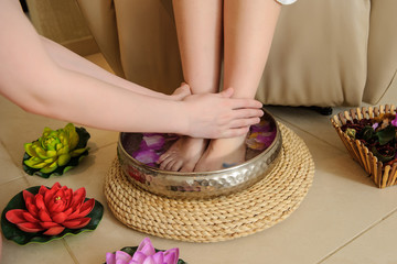 lateral view of a woman's foot washing procedure before spa treatment in a salon done by a masseuse; a silver bowl with water, rose petals and flowers arround