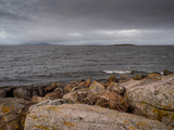 Hare island in Galway bay, Burren mountain in the background, Dramatic moody sky. Nobody, West coast of Ireland.