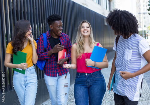 canvas print picture Group of four international students walking to university