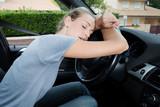 tired woman sleeping on steering wheel in car