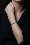 Female, silver, wicker, bracelet with diamonds in the middle on woman hand, on black background