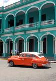 Ville de Santa Clara, vieille voiture américaine orange devant bâtiment vert à colonnes, Cuba, caraïbes
