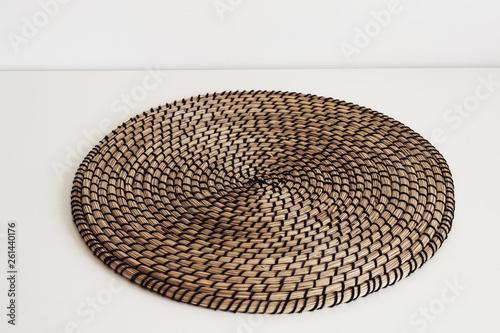 Wicker straw decor napkin on white table. Scandinavian interior fragment © colnihko