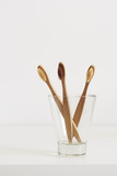 Bamboo toothbrushes with natural bristles in glass in Scandinavian style bathroom