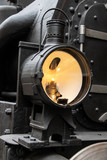 An old lamp of a steam locomotive shines to forward on track. Retro light in front part of train.