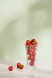 Fresh raspberries in a glass beaker isolated on light background