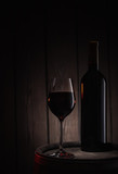 Bottle and glass of red wine stand on old wooden barrel