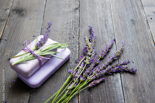 lavender soap and flowers on old black wooden table