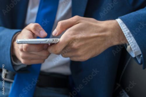 Leinwanddruck Bild business man closeup with mobile phone