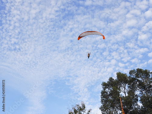 A man flying in the beautiful blue cloudy sky, parachute with a motor, paramotor. Sky driving. Extreme sport, adventure, freedom concept. © supakvadee
