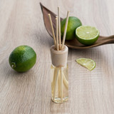 Aromatic reed air freshener with the aroma of fresh lime on a wooden table. Selective focus.