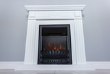 White wooden decorative electric fireplace with a beautiful burning flame. Interior photo on gray background.