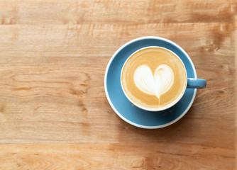 Top view of hot Coffee cup with a barista art heart shape foam on wooden table background with copy text space.
