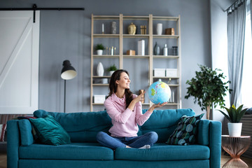 Smiling beautiful woman is looking at a model of the globe sitting on a sofa.