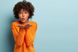 Beautiful black girl makes air kiss, blows over two palms, wants to kiss man, has healthy skin, wears orange jumper, poses against blue background with empty space for your promotional content