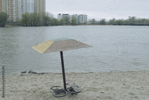 old umbrella by the lake - 261543348