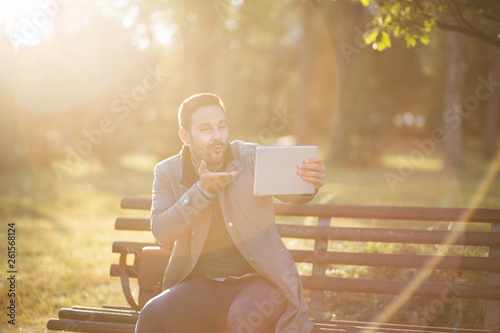 canvas print picture Handsome man make video call while using tablet