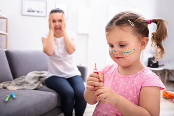 Shocked Mother Looking At Her Daughter Painting Face