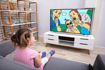 Little Girl Sitting On Sofa Watching Cartoon