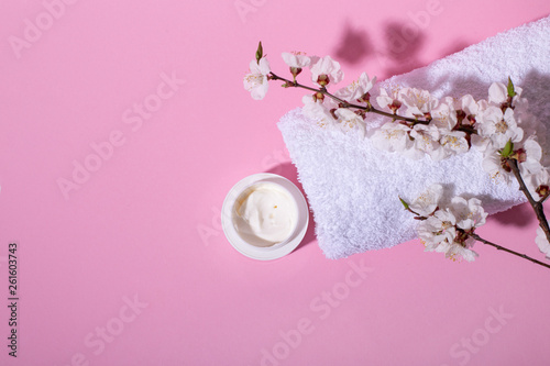 canvas print picture Beautiful Spa and wellness composition with natural flower blossom, creme and towel on pink background.