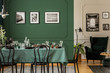 Black and white posters on green wall of stylish dining room interior with log table with wine glasses, plates and cones