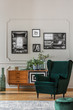 Emerald green armchair in elegant living room with black and white photos on grey wall and retro cabinet