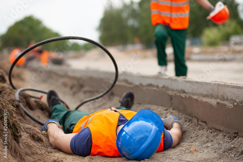 Closeup of injured road construction worker lying on the ground
