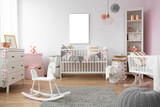 White rocking horse on grey rug in child's bedroom interior with mockup on empty poster. Real photo