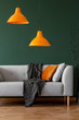 Quadro Orange lamps on a green wall and sofa in a simple living room interior