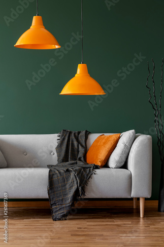 canvas print picture Orange lamps on a green wall and sofa in a simple living room interior