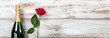 Anniversary background with red rose and champagne on white weathered wood