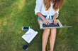 Top view of woman sitting in park on the green grass with laptop, notebook and smartphone, hands on keyboard.