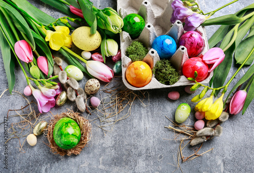 Colorful flowers and painted Easter eggs on grey, stone background