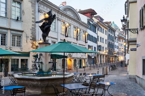 canvas print picture Zürich Neumarkt, Abenddämmerung, Zürcher Altstadt, Jupiterbrunnen, historische Stätte, alte Häuser und Strassenlampen, Tische, Stühle, Hintergrund Universität Zürich