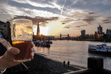 Hand holds a half drunk pint glass of typical London beer or ale against a stunning background of the iconic buildings of London at sunset
