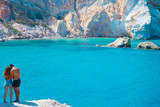 A couple is gazing at the turquoise waters of the bay of Firopotamos village in Milos greek island in Greece